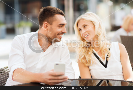 happy couple with smatphone at city street cafe stock photo, love, date, technology, people and relations concept - smiling happy couple with smatphone at city street cafe by Syda Productions