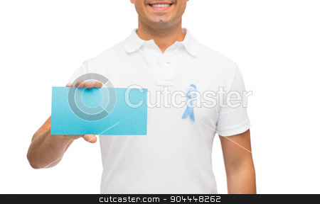 man with prostate cancer awareness ribbon and card stock photo, medicine, health care, gesture and people concept - close up of middle aged man in t-shirt with sky blue prostate cancer awareness ribbon holding blank paper card by Syda Productions