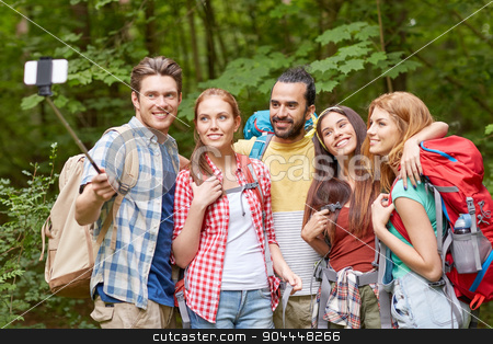 friends with backpack taking selfie by smartphone stock photo, technology, travel, tourism, hike and people concept - group of smiling friends walking with backpacks taking picture by smartphone on selfie stick in woods by Syda Productions