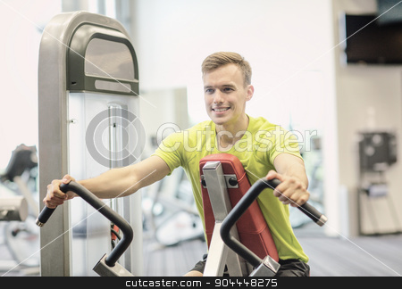 smiling man exercising in gym stock photo, sport, fitness, lifestyle and people concept - smiling man exercising in gym by Syda Productions
