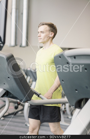 man with smartphone exercising on treadmill in gym stock photo, sport, fitness, lifestyle, technology and people concept - man with earphones exercising on treadmill in gym by Syda Productions