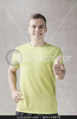 smiling man in gym stock photo, sport, fitness, lifestyle and people concept - smiling man showing thumbs up in gym by Syda Productions