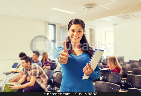 group of smiling students in lecture hall stock photo, education, high school, gesture and people concept - group of smiling students with notepads showing thumbs up in lecture hall by Syda Productions
