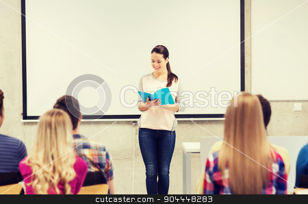 group of smiling students in classroom stock photo, education, high school, teamwork and people concept - smiling student girl with notebook standing in front of students in classroom by Syda Productions
