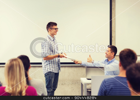 group of students and smiling teacher with notepad stock photo, education, high school, technology and people concept - smiling student with notepad, laptop computer standing in front of teacher showing thumbs up gesture in classroom by Syda Productions