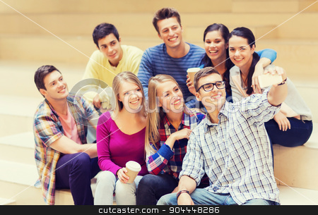 group of students with smartphone and coffee cup stock photo, education, friendship, drinks, technology and people concept - group of smiling students with smartphone and paper coffee cup taking selfie at school by Syda Productions