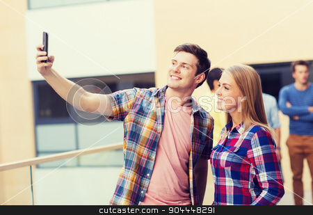 group of smiling students outdoors stock photo, friendship, people, technology and education concept - group of smiling students with smartphone taking selfie outdoors by Syda Productions