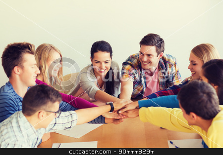 group of smiling students with hand on top stock photo, education, teamwork and people concept - smiling students with papers putting hands on top of each other by Syda Productions