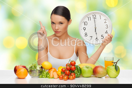 woman with healthy food and clock warning stock photo, people, eating and diet concept - woman with healthy food holding big clock, pointing finger up and warning over green lights background by Syda Productions