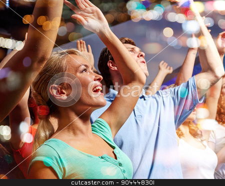 smiling friends at concert in club stock photo, party, holidays, celebration, nightlife and people concept - smiling friends waving hands at concert in club by Syda Productions