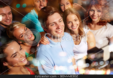 friends with smartphone taking selfie in club stock photo, party, technology, nightlife and people concept - smiling friends with smartphone and monopod taking selfie in club by Syda Productions