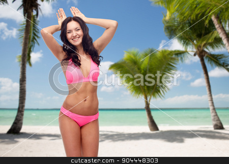 happy young woman in pink bikini swimsuit on beach stock photo, people, travel, summer and sexual concept - happy young woman in pink bikini swimsuit making bunny ears gesture over tropical beach with palm trees background by Syda Productions