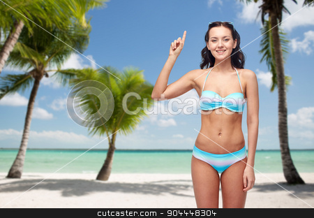 happy woman in bikini pointing finger up on beach stock photo, people, travel, swimwear and summer concept - happy young woman in bikini swimsuit pointing finger up to something imaginary over tropical beach with palm trees background by Syda Productions