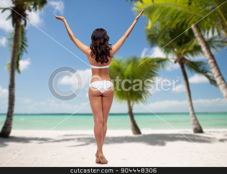 woman in white bikini swimsuit on tropical beach stock photo, people, fashion, beauty, summer and travel concept - young woman posing in white bikini swimsuit with raised hands from back over tropical beach with palm trees background by Syda Productions