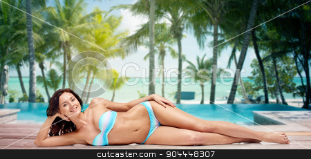 happy woman lying in bikini swimsuit on beach stock photo, people, fashion, swimwear, summer and beach concept - happy young woman lying in bikini swimsuit over tropical beach with palm trees and pool at hotel resort background by Syda Productions