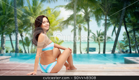 happy young woman sunbathing in bikini on beach stock photo, people, fashion, swimwear, summer and beach concept - happy young woman sunbathing in bikini swimsuit over tropical beach with palm trees and pool at hotel resort background by Syda Productions