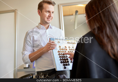 woman choosing hair color from palette at salon stock photo, beauty, hair dyeing and people concept - happy young woman with hairdresser choosing hair color from palette samples at salon by Syda Productions