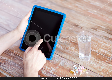 close up of hands with tablet pc, pills and water stock photo, medicine, technology, nutritional supplements and people concept - close up of male hands pointing finger to blank tablet pc computer screen, pills and water on table by Syda Productions