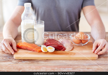 close up of male hands with food rich in protein stock photo, sport, fitness, healthy lifestyle, diet and people concept - close up of male hands with food rich in protein on cutting board on table by Syda Productions