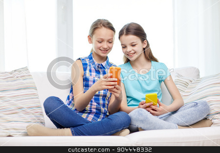 happy girls with smartphones sitting on sofa stock photo, people, children, technology, friends and friendship concept - happy little girls with smartphones sitting on sofa at home by Syda Productions