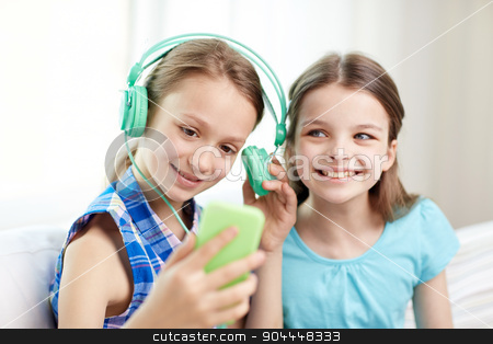 happy girls with smartphone and headphones stock photo, people, children, technology, friends and friendship concept - happy little girls with smartphone and earphones sitting on sofa and listening to music at home by Syda Productions