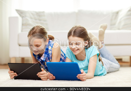 happy girls with tablet pc lying on floor at home stock photo, people, children, technology, friends and friendship concept - happy little girls with tablet pc computers lying on floor at home by Syda Productions