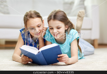 two happy girls reading book at home stock photo, people, children, friends, literature and friendship concept - two happy girls lying on floor and reading book at home by Syda Productions