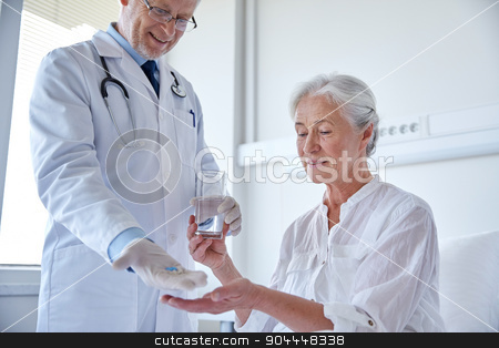 doctor giving medicine to senior woman at hospital stock photo, medicine, age, health care and people concept - doctor giving medication and water to senior woman at hospital ward by Syda Productions
