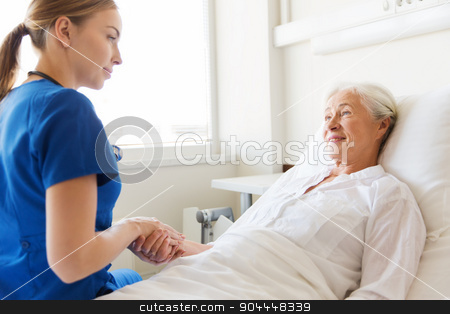 doctor or nurse visiting senior woman at hospital stock photo, medicine, age, support, health care and people concept - doctor or nurse visiting and cheering senior woman lying in bed at hospital ward by Syda Productions