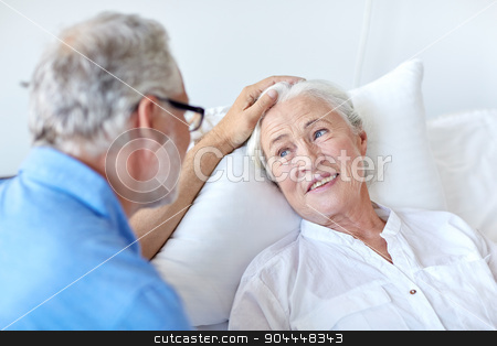 senior couple meeting at hospital ward stock photo, medicine, age, support, health care and people concept - happy senior man visiting and cheering his woman lying in bed at hospital ward by Syda Productions