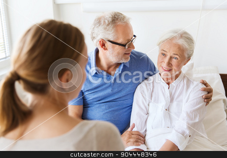happy family visiting senior woman at hospital stock photo, medicine, support, family health care and people concept - happy senior man and young woman visiting and cheering her grandmother lying in bed at hospital ward by Syda Productions