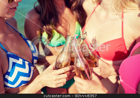 close up of happy young women with drinks on beach stock photo, summer vacation, holidays, party, travel and people concept - close up of happy young women with drinks clinking bottles on beach by Syda Productions