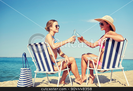 happy women clinking bottles and drinking on beach stock photo, summer vacation, travel and people concept - happy women drinking beer and sunbathing in lounges on beach by Syda Productions