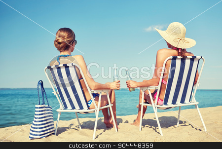 happy women sunbathing in lounges on beach stock photo, summer vacation, travel and people concept - happy women drinking beer and sunbathing in lounges on beach by Syda Productions