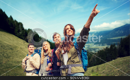 group of smiling friends with backpacks hiking stock photo, adventure, travel, tourism, hike and people concept - group of smiling friends with backpacks pointing finger over alpine hills background by Syda Productions