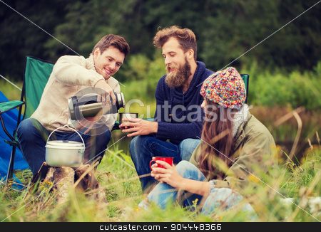 group of smiling friends cooking food outdoors stock photo, adventure, travel, tourism and people concept - group of smiling friends cooking food in dixie sitting around bonfire outdoors by Syda Productions