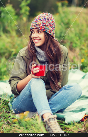 smiling young woman with cup sitting in camping stock photo, adventure, travel, tourism, hike and people concept - smiling young woman with cup sitting in camping by Syda Productions