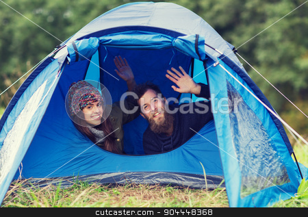 smiling couple of tourists looking out from tent stock photo, camping, travel, tourism, hike and people concept - smiling couple of tourists looking out from tent and waving hands by Syda Productions