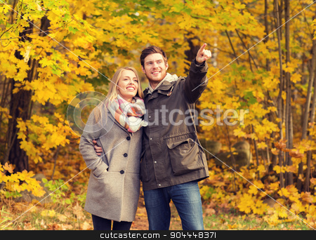 smiling couple hugging in autumn park stock photo, love, relationship, family and people concept - smiling couple hugging and pointing finger in autumn park by Syda Productions