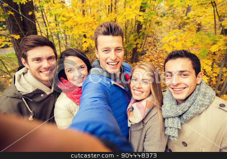 group of smiling men and women in autumn park stock photo, technology, season, friendship and people concept - group of smiling men and women taking selfie with smartphone or camera in autumn park by Syda Productions
