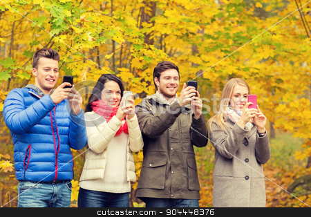 smiling friends with smartphones in city park stock photo, season, people, technology and friendship concept - group of smiling friends with smartphones taking picture in autumn park by Syda Productions