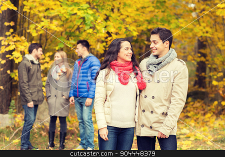group of smiling men and women in autumn park stock photo, love, relationship, season, friendship and people concept - group of smiling men and women walking in autumn park by Syda Productions