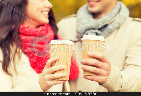 smiling couple with coffee cups in autumn park stock photo, love, season, drinks and people concept - close up of happy smiling couple with coffee cups in autumn park by Syda Productions