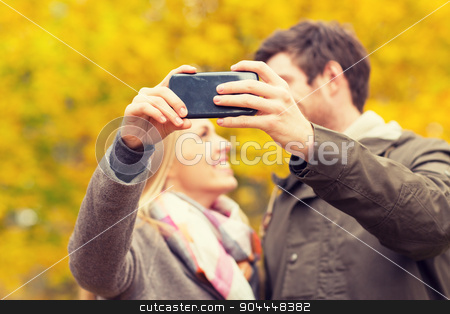 couple taking selfie with smartphone in park stock photo, technology, love, relationship and people concept - close up of smiling couple taking selfie with smartphone in autumn park by Syda Productions
