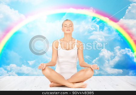 woman meditating in yoga lotus pose stock photo, people, health, wellness and meditation concept - woman in underwear meditating in yoga lotus pose on wooden floor over white clouds and rainbow on blue sky background by Syda Productions