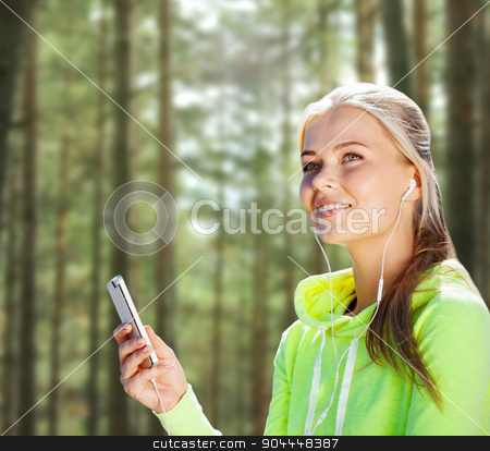 happy woman with smartphone and earphones stock photo, people, sport, fitness and technology concept - happy woman with smartphone and earphones listening to music over woods background by Syda Productions