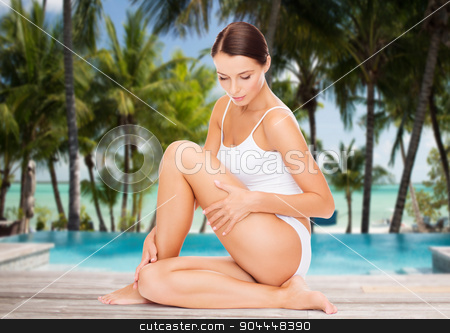 beautiful woman touching her hips over beach stock photo, people, beauty, spa, travel and resort concept - beautiful woman in cotton underwear touching her hips over swimming pool on beach with palms background by Syda Productions