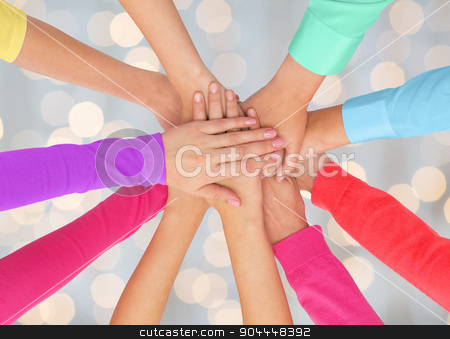 close up of women hands on top in rainbow clothes stock photo, people, gesture, gay pride and homosexual concept - close up of women hands in rainbow clothes on top of each other over holidays lights background by Syda Productions