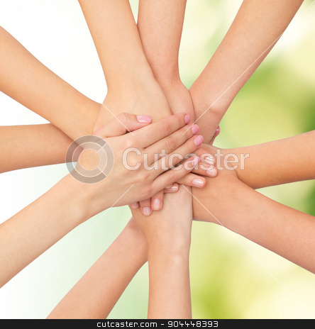 close up of hands on top stock photo, healthcare, people, gesture and medicine concept - close up of women hands on top of each other over green background by Syda Productions