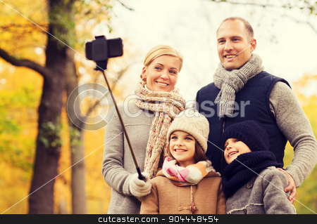 happy family with smartphone and monopod in park stock photo, family, childhood, season, technology and people concept - happy family photographing with smartphone and selfie stick in autumn park by Syda Productions